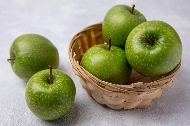 白い背景の上のバスケットの側面図青リンゴ