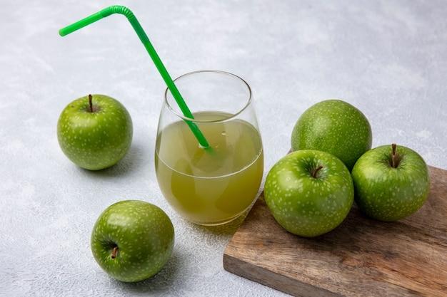 Vista laterale mele verdi con succo di mela in un bicchiere e una cannuccia verde su sfondo bianco