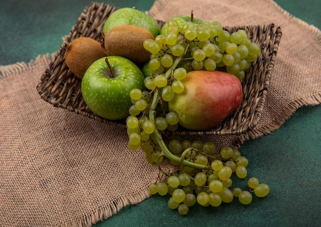 緑の背景にベージュのナプキンのスタンドにブドウキウイと梨と青リンゴの側面図