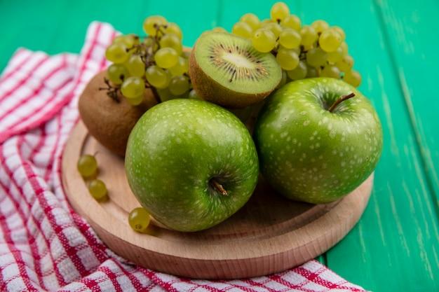 Вид сбоку зеленые яблоки с киви и зеленым виноградом на подставке на красном клетчатом полотенце на зеленом фоне