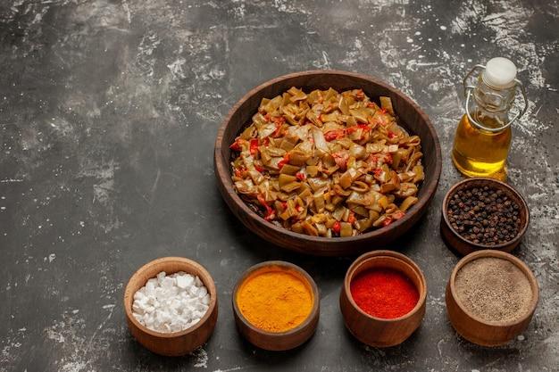 側面図サヤインゲンのニンニクボウルのスパイスオイルのボトルとサヤインゲンとトマトのプレートのテーブル