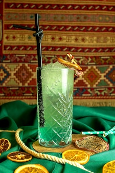 Side view of green cocktail witn rum and mint in a glass decorated with dried orange slices on green
