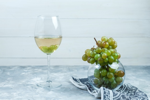 Side view green grapes in glass pot with a glass of wine, kitchen towel on wooden and grungy grey background. horizontal