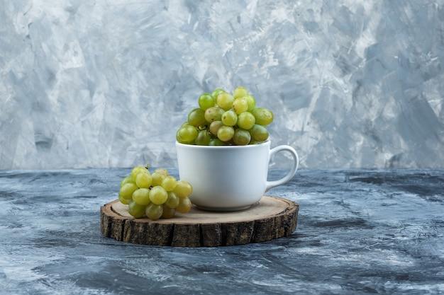 지저분한 석고와 나무 조각 배경에 흰색 컵에 측면보기 녹색 포도. 수평
