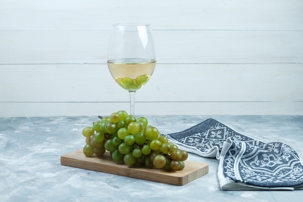 Side view green grapes with a glass of wine, wood piece, kitchen towel on wooden and grungy grey background. horizontal