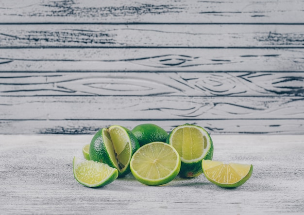 Side view green lemons with slices on gray wooden background. horizontal