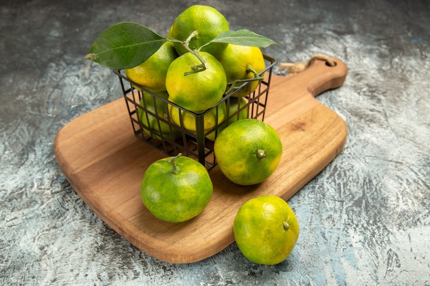 Side view of green mandarins with leaves inside and outside of a basket on wooden cutting board on gray table
