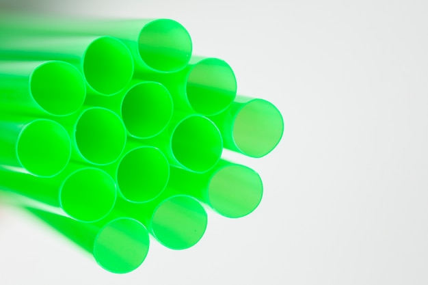 Side view green plastic drinking straws