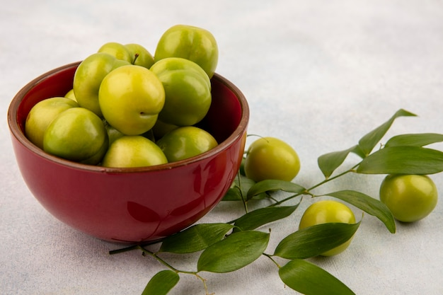 Side view of green plums in bowl with leaves on white background