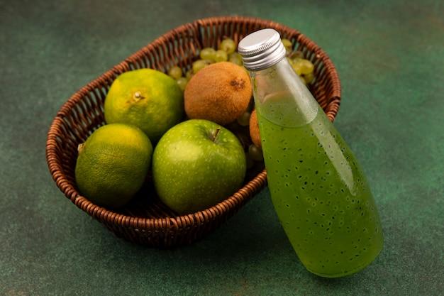 緑の壁にジュースのボトルとバスケットにリンゴキウイとブドウと緑のタンジェリンの側面図
