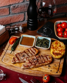 Side view of grilled beef steak with baked potato and sauce on a wooden board