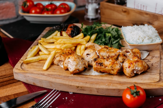 Side view of grilled chicken meat and vegetables with french fries and herbs on a wooden board