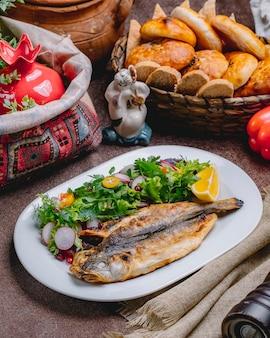 Вид сбоку жареной рыбы с салатом из овощей и зелени с ломтиком лимона
