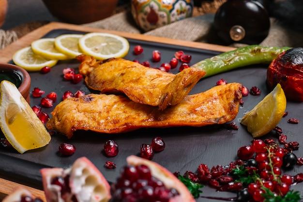 Vista laterale pesce grigliato con pomodoro e peperoncino grigliato con fette di limone melograno e salsa narsharab