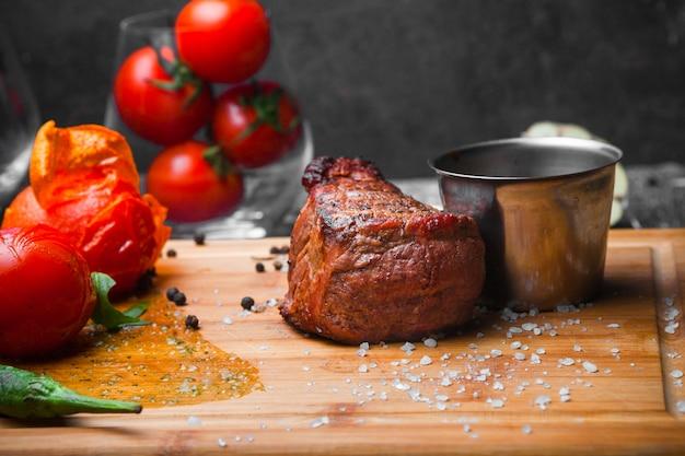 Vista laterale grigliata di carne con pomodoro e carta e salsa a bordo di bistecca