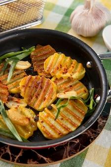 Вид сбоку жареной картошки с зеленью черного перца и чесноком на скатерть