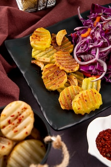 Side view grilled potatoes with red onion cabbage red orange peppers and dried chili flakes on dark grey background