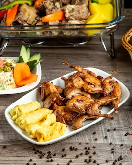 Side view of grilled quail with lula kebab from potatoes served with vegetable salad on the table