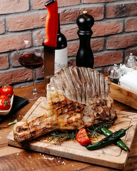 Side view of grilled ribs served with vegetables on wooden board