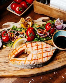 Side view of grilled salmon with fresh tomatoes lemonnd herbs with narsharab sauce on wooden board