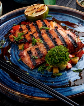 Side view of grilled salmon with vegetables lemon and soy sauce on a plate on wood table
