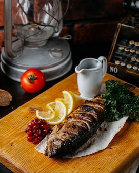 Side view of grilled trout with lemon and pomegranate seeds on a wooden cutting board