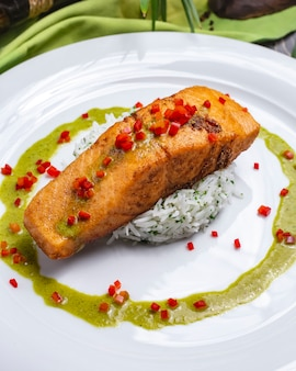 Side view grillled fish fillet with rice garnish sauce and chilli pepper on a plate