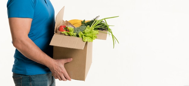 Side view of grocery box held by delivery man