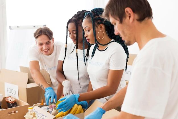 寄付の世話をするボランティアの側面図グループ