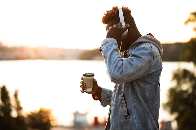 Side view guy with headphones and coffee cup