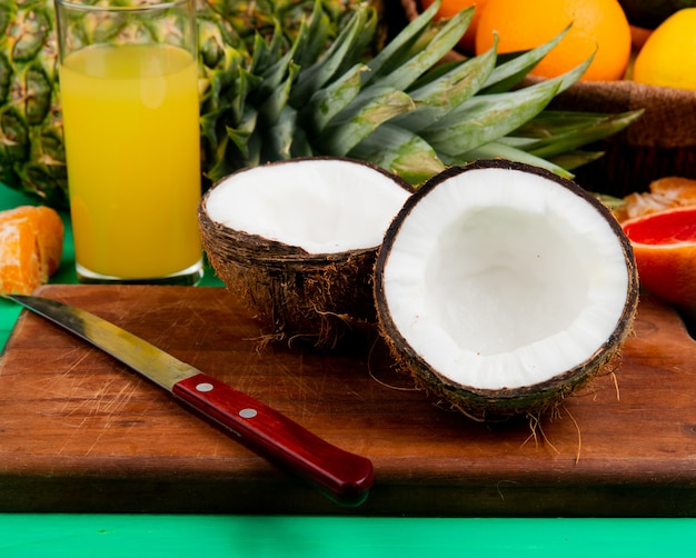 Side view of half cut coconut and knife on cutting board with other citrus fruits and orange juice on green background