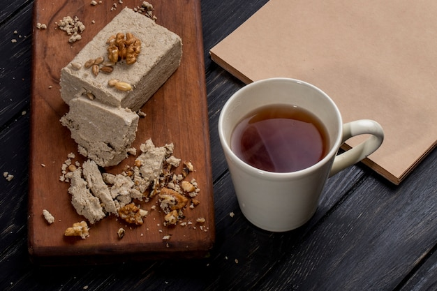 Side view of halva with sunflower seeds and walnuts on a wooden board and a cup of tea on rustic