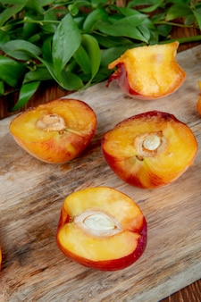 Side view of halves of fresh ripe peaches on a wooden cutting board with green leaves on rustic table
