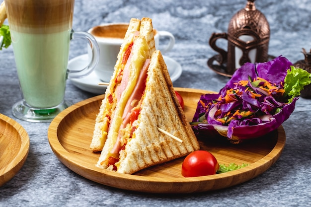 Side view ham and cheese sandwich with tomato greens carrot and red cabbage on a board