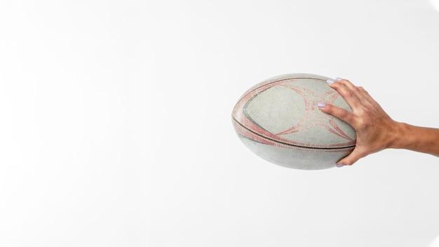 Vista laterale della mano che tiene la palla da rugby con lo spazio della copia