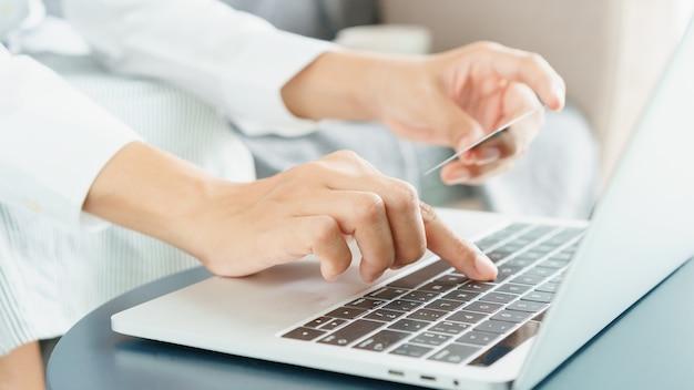 側面図。若い女性の手がクレジットカードでオンラインで購入しています。