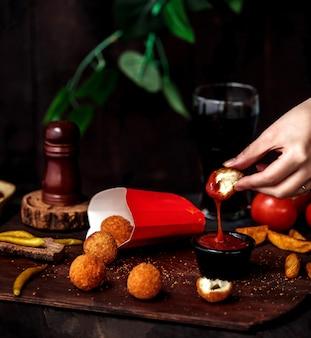 Vista laterale di una mano che mette la palla di formaggio fritta nel ketchup