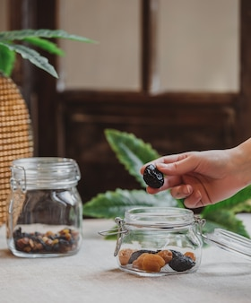 Side view of hand putting prunes into a glass jar with dried plums