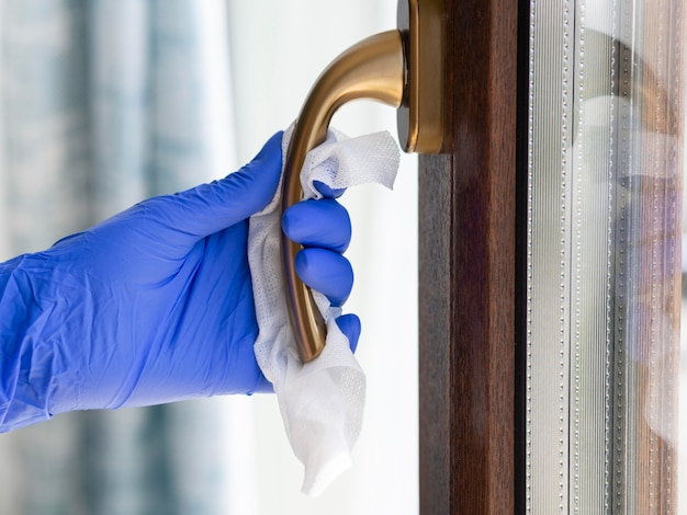 Side view of hand with surgical glove cleaning handle with napkin