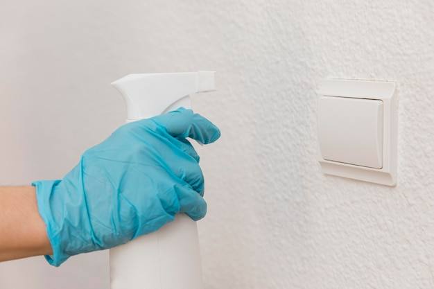 Side view of hand with surgical glove spraying disinfectant on light switch
