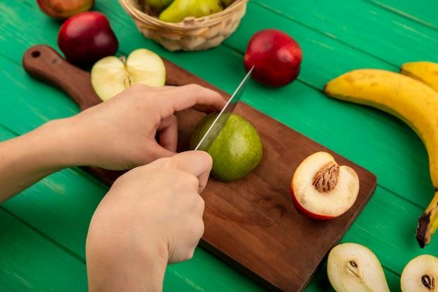 Vista laterale delle mani che tagliano la mela con un coltello e mezza pesca sul tagliere con banana e mezza pera tagliata su sfondo verde