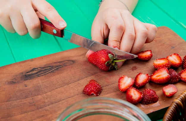 Side view of hands cutting strawberries with knife on cutting board on green surface