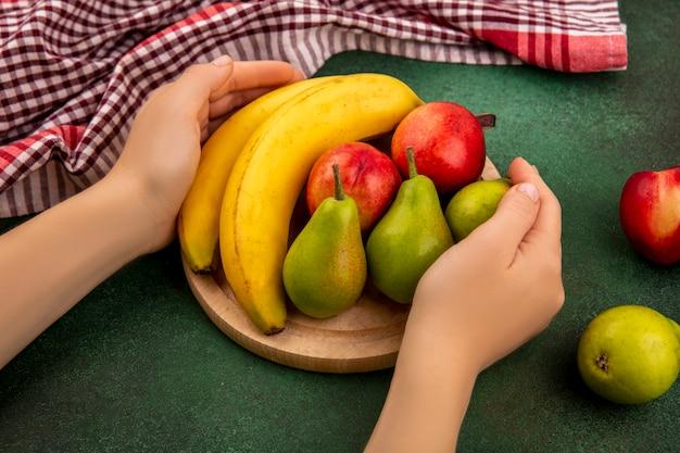 Vista laterale delle mani che tengono il tagliere con frutta su di esso come banana pera pesca con panno plaid su sfondo verde