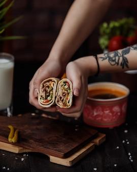 La vista laterale delle mani che tengono il doner ha riempito di sottaceti e salsa di verdure di pollo avvolti in lavash