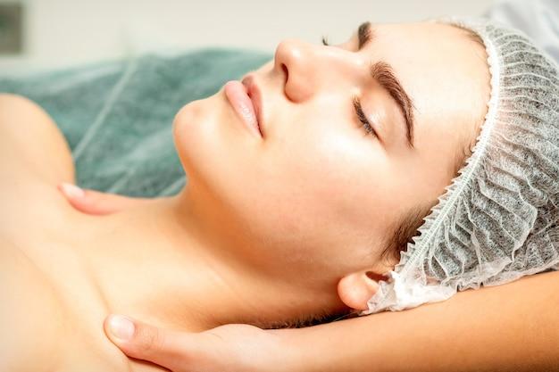 スパ美容院で若い白人女性に首と肩のマッサージをしている女性セラピストの側面図の手