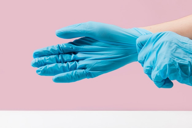 Side view of hands putting on surgical gloves