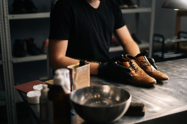 Side view of hands of shoemaker shoemaker in black gloves holding old worn light brown leather shoes