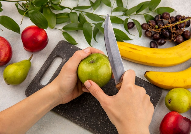 Side view of hands slicing apple with knife on cutting board and grape pear banana peach with leaves on white background