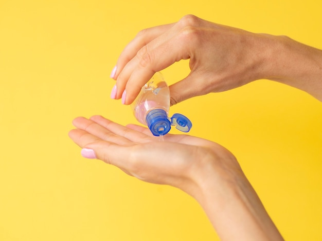 Side view of hands using hand sanitizer