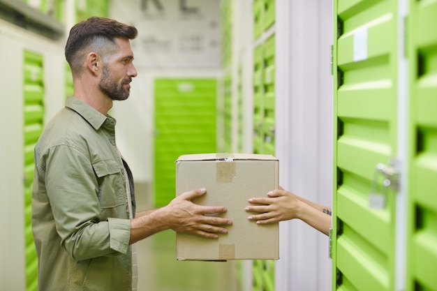 Side view at handsome bearded man holding cardboard box and handing in to woman while packing self storage unit, copy space